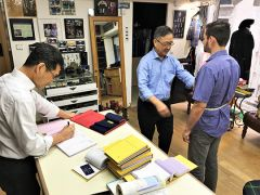 Brotherly master tailors Johnny (left) and Bonny Yuen measure Max Dickstein for a bespoke blazer. Photo by David Dickstein