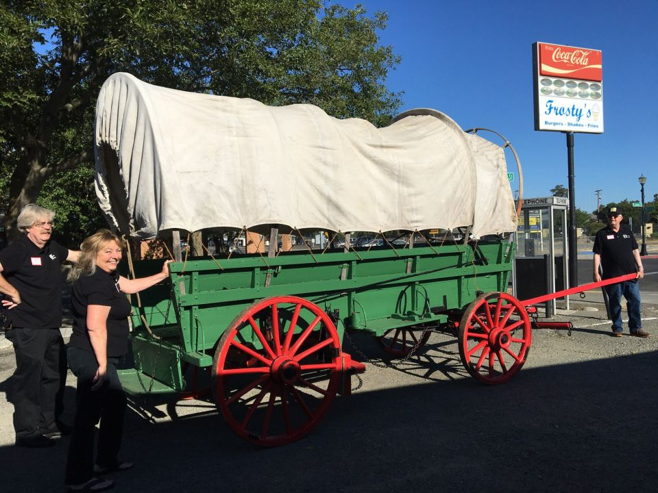 Museum Director Gary Erwin, 2nd Vice President Carol Abrams and President Bill Schroeder help wheel the old wagon train from Frosty's parking lot to the museum front. Photo by Debra Dingman