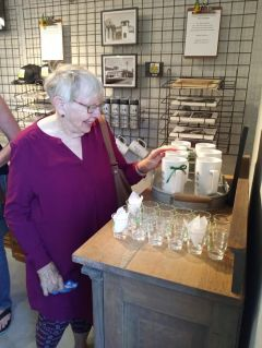 Jewel Fink discovers museum mementos such as engraved glasses, cups, calendars, and hats to purchase. Photo by Debra Dingman